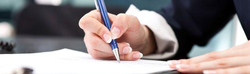 Manos-de-mujer-con-un-boligrafo-firmando-unos-papeles-encima-de-una-mesa-1010x300
