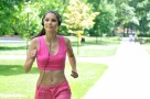 Young person (woman) with headphones listening music running outdoors in park on sunny day